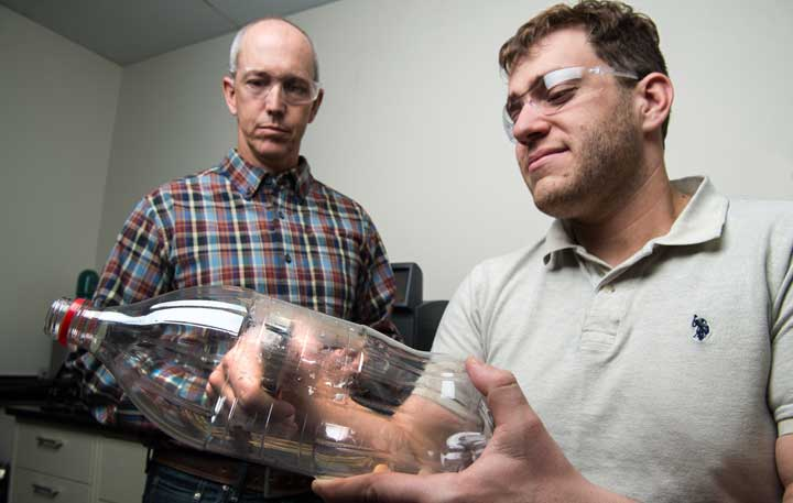 NREL's Bryon Donohoe and Nic Rorrer punch out coupon samples from a PET bottle to test how effectively the PETase enzyme digests plastic. Photo Dennis Schroeder/NREL