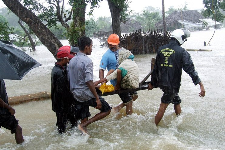 Woman carried to safety after monsoon flooding in Sri Lanka in 2008 Photo: trokilinochchi