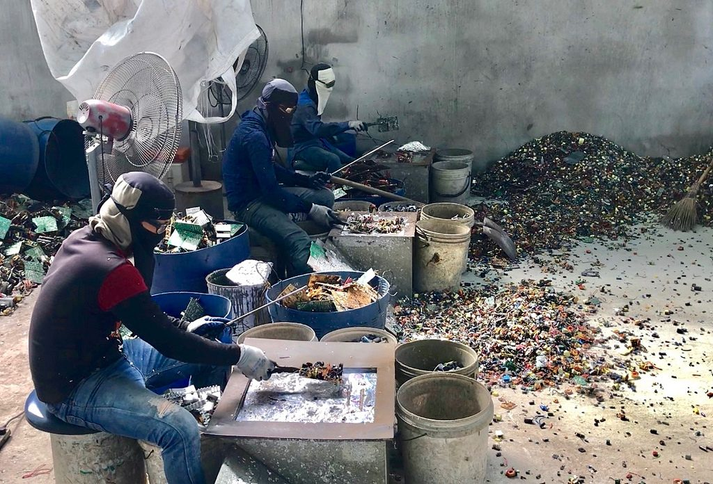 Burmese workers trying to protect themselves from the fume and smoke from the cooking of circuit boards in a primitive site in Thailand receiving e-waste from North America and Europe. Copyright BAN, February 2018.
